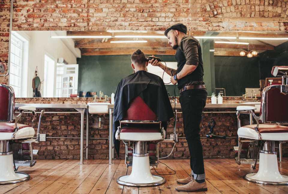 Barbier schneidet Mann die Haare